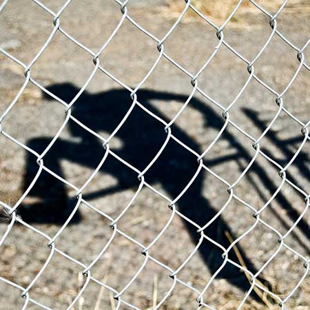 shadow of person climbing fence